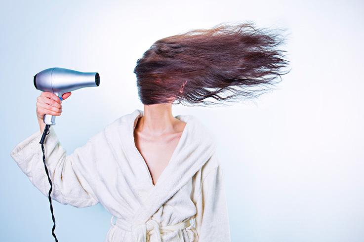 Strom im Badezimmer - eine Frau föhnt sich die Haare